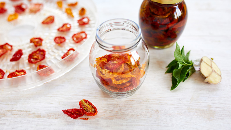 Dehydrated tomatoes in a jar, next to a dehydrator tray