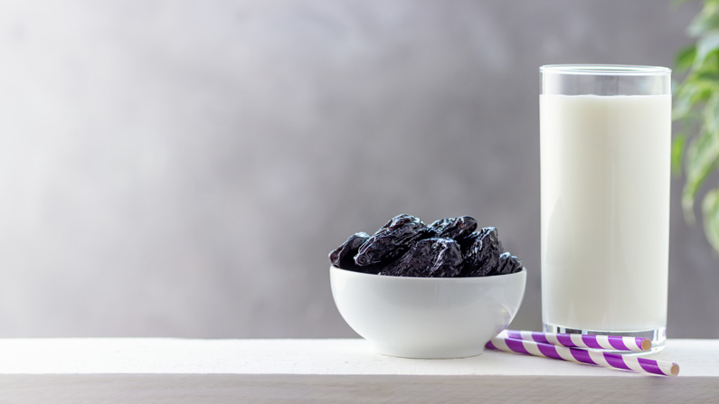 prunes in a bowl next to a glass of milk